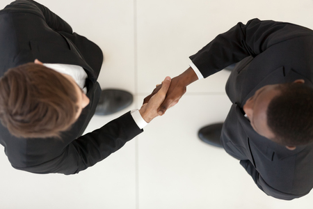 Directly from above diverse businessmen wearing suits standing shaking hands after effective successful negotiations. Top view black and caucasian colleagues handshaking gesture of greeting, farewell Stock Photo