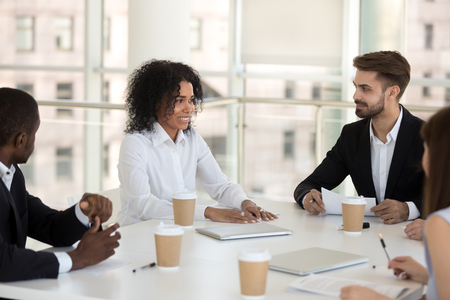 Biracial mixed race team leader presenting new business idea talking to diverse multiracial colleagues company staff during meeting sitting at desk in modern office conference room. Teamwork concept Stock Photo