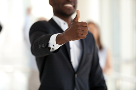 Satisfied happy black african american businessman in suit showing thumbs up, close up focus on hand finger up. Gesture and symbol of success in business, market leadership and great results in work