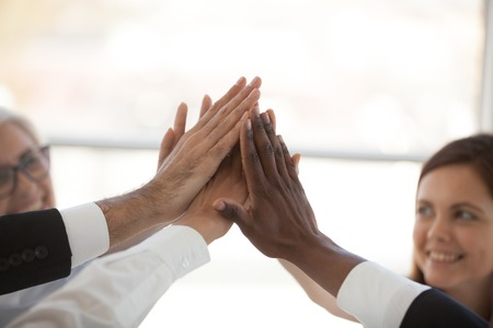 Happy motivated multiracial businesswoman and businessman giving high five stack their hands together celebrating victory sharing success and great deal. Goal achievement unity and teamwork concept Banco de Imagens - 117645596