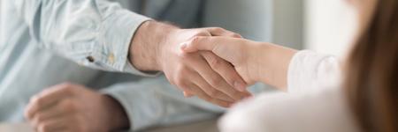 Empresario estrecharme la mano con gesto de saludo de empresaria, cliente y agente. Apretón de manos de dos personas expresando respeto y concepto de confianza. Banner de foto de cierre horizontal para diseño de encabezado de sitio web Foto de archivo