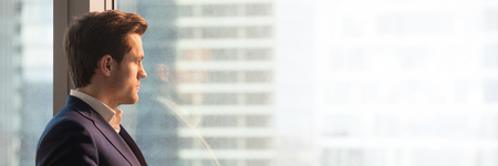 Panoramic image businessman in suit looks through office window at big city modern building architecture dream about future. Horizontal photo banner for website header design with copy space for text 写真素材