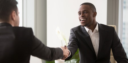 African boss shake hands with business partner gather at office for negotiations, job interview human resources, client and executive manager concept, horizontal photo banner for website header design Foto de archivo