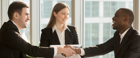 Horizontal photo three business people gather at modern office, african employee handshaking with caucasian partner, nice to meet you, successful negotiations concept banner for website header design