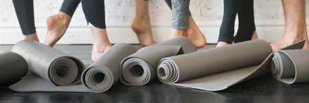 Horizontal photo people standing after work out, close up yoga mats grey carpets in roll and athlete barefoot legs. Group training, active lifestyle in club concept. Banner for website header design