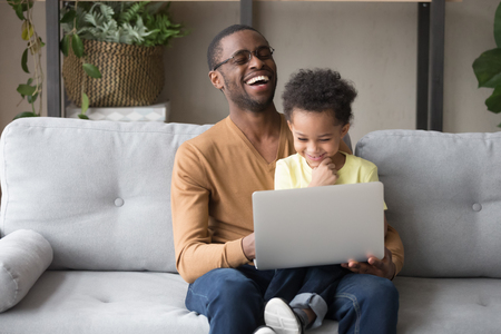 Happy black dad watching funny cartoons movie with little toddler son sitting on couch, african father and cute small kid boy having fun with computer, daddy and child laughing using laptop at home Фото со стока