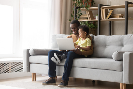 Young black father and kid son using laptop at home for child education looking at pc screen doing online shopping at home, smiling african dad and toddler boy study learning computer watching video