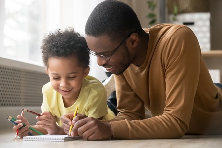 African dad and little creative toddler kid son draw with colored pencils lying on warm floor together, black father baby sitter teaching help child boy learning playing at home, babysitting concept