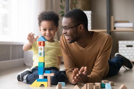 Fröhlicher süßer kleiner Sohn, der ein Spiel mit einem schwarzen Papa-Babysitter-Bauturm aus bunten Holzblöcken spielt, ein afrikanischer Familienvater und ein Kleinkind,