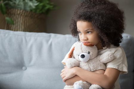 Molesto solitario acosado pequeño niño afroamericano niña sosteniendo un oso de peluche mirando a otro lado se siente abandonado abusado, triste solo preescolar raza mixta niño huérfano abrazando peluche, concepto de adopción de caridad