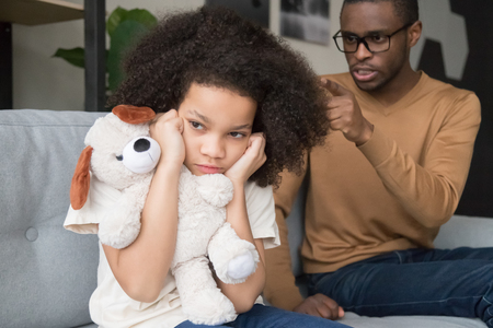 Stubborn naughty african preschool child girl closing ears ignoring angry strict black dad scolding yelling reprimand kid daughter for rude disrespect mistake, parents children family fight concept