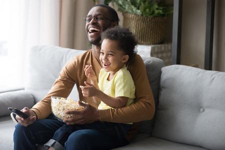 Felice papà afroamericano e figlio del bambino che ridono tenendo in mano il telecomando dei popcorn guardando uno spettacolo televisivo divertente di film comici seduto sul divano, padre nero che si diverte con il bambino che guarda la televisione a casa