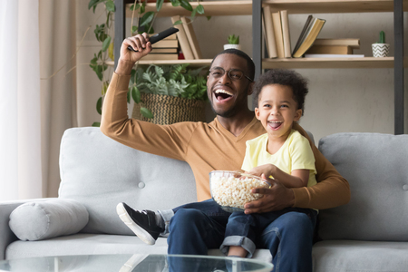 Excited black father with toddler son fans watching football sport tv game celebrating goal, happy african dad and little kid child cheering favorite soccer team victory at home sitting on couch 版權商用圖片