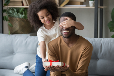 Cute african kid daughter closing eyes congratulating black dad with happy birthday giving gift box sitting on sofa, child girl making surprise preparing present on fathers day having fun with daddy 版權商用圖片 - 117788493