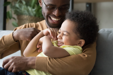 Affectionate loving african dad holding tickling child toddler son, happy playful black father and mixed race kid boy embracing having fun laughing cuddling enjoy positive emotions playing together