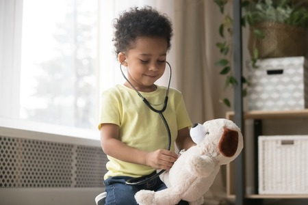 Cute little toddler african american boy playing funny game as doctor holding stethoscope listening to toy, mixed race black preschool child kid pretending nurse treating fluffy patient at home Stock Photo
