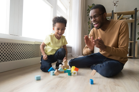 Happy joyful african dad and little toddler son laughing playing with wooden blocks sit of warm floor, cheerful black father baby sitter having fun with kid boy enjoy child activity at home together Banco de Imagens