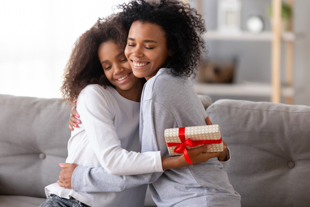 Relative people sitting on couch at home, african mother embracing teen daughter congratulating lovely child with birthday or special occasion. Love and attention, best wishes and life events concept