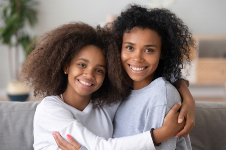 Head shot portrait of biracial daughter and young mommy sitting on couch at home and embracing celebrating mothers day. New mom for adopted teen kid, relative people elder and younger sisters concept Stock Photo