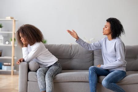 Une mère africaine noire réprimande les gens de sa fille adolescente assis sur un canapé à la maison. Conflit entre sœurs plus âgées et plus jeunes, problèmes d'adolescents, incompréhension des différentes générations, concept de relations parent-enfant