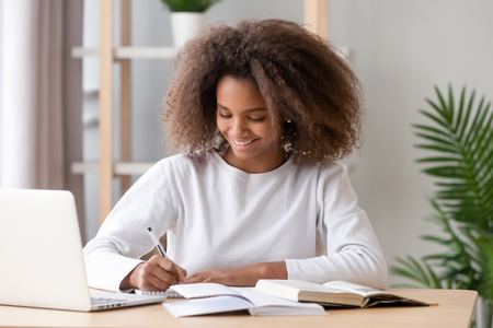 Diligent schoolgirl sitting at home or classroom, desk filled with books training materials, teen study with laptop writing using textbook preparing for test at school. Education and knowledge concept Stock Photo