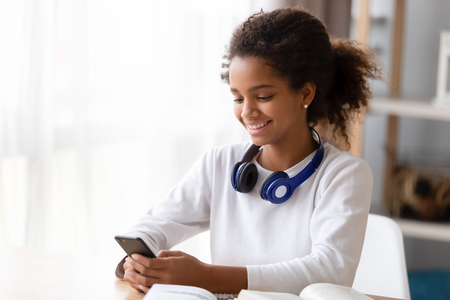 Black teen girl studying use training materials books she distracted from learning holds mobile phone chatting with friend surfing internet. Generation addicted with gadgets everyday overuse concept