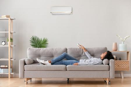 Afrikaanse ontspannen vrouw in vrijetijdskleding liggend op de bank in de woonkamer in een modern huis met de afstandsbediening van de airconditioner, stelt een comfortabele ideale optimale luchttemperatuur in, geniet van het ademen van frisse lucht Stockfoto