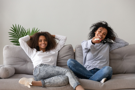 Happy african mother hold remote control switch channels resting with teen daughter sitting on sofa at home. Older younger sisters, adolescent and nanny sets air conditioner making comfort temperature