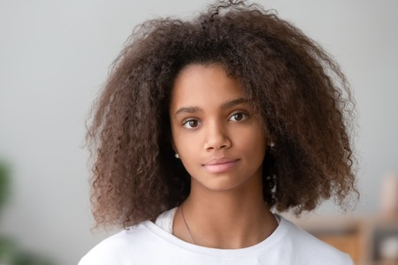 Head shot portrait healthy attractive mixed race adolescent teen girl with curly ringlets hairstyle and pretty face posing indoor looking at camera. Natural beauty innocence and new generation concept Standard-Bild