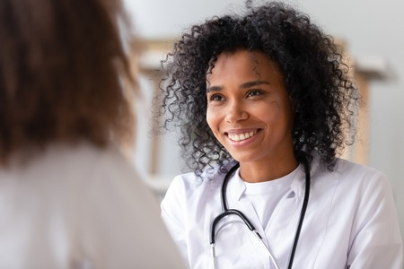 Close up focus on african smiling woman doctor in white coat stethoscope on neck look at patient listen examine health. Adolescent medicine hebiatrics or paediatrics, healthcare medical worker concept