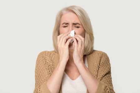 Ill allergic old mature woman blowing runny nose got hay fever rhinitis allergy flu, sick middle aged senior lady sneezing in tissue holding handkerchief isolated on white grey studio background Standard-Bild
