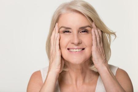Gelukkig volwassen oudere vrouw aanraken gezicht gezonde zachte gehydrateerde gehydrateerde huid geïsoleerd op grijze studio achtergrond, glimlachend middelbare leeftijd senior dame natuurlijke schoonheidsbehandeling anti veroudering concept, portret Stockfoto