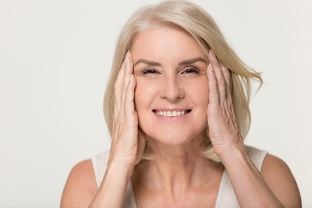 Szczęśliwa dojrzała starsza kobieta dotyka twarzy zdrowej, miękkiej, nawilżonej, nawilżonej skóry na białym tle na szarym tle studio, uśmiechając się w średnim wieku starsza pani naturalny zabieg kosmetyczny anty starzenie się koncepcja, portret Zdjęcie Seryjne