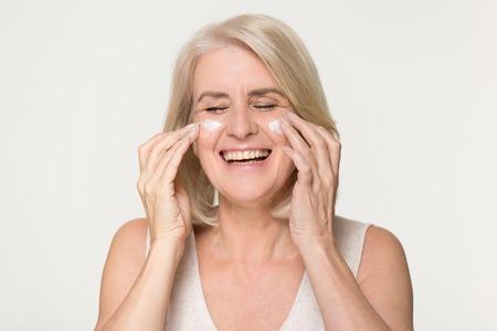 Felice sana vecchia donna matura ridere applicare anti invecchiamento crema cosmetica idratante sul viso, sorridente signora di mezza età morbida pulita cura della pelle naturale lozione di trattamento di bellezza isolato su sfondo studio