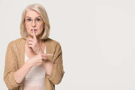 Old mature woman holding finger on lips mouth keep it quiet secret information pointing at copy space, middle aged senior lady showing hush shh shush gesture isolated on white grey studio background