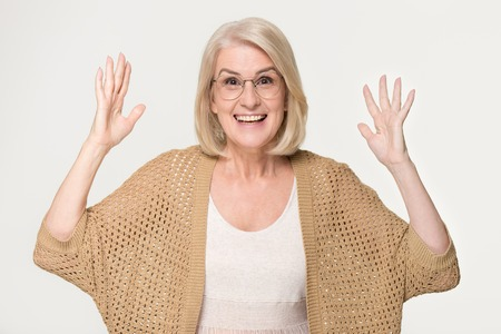 Excited ecstatic middle aged mature woman feeling amazed by win victory great news overjoyed looking at camera, happy euphoric senior old lady grandma winner isolated on grey white studio background