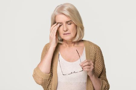 Sconvolto stanco vecchia donna matura che si toglie gli occhiali sensazione di affaticamento della vista dolore, signora anziana stressata soffre di mal di testa cattiva visione affaticamento degli occhi problema di affaticamento isolato su sfondo grigio bianco studio