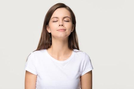 Feliz chica adolescente tranquila que disfruta de un buen olor o una fragancia agradable, una mujer joven serena y consciente que toma una respiración profunda no siente estrés inhalando aire fresco relajante aislado sobre fondo gris blanco de estudio
