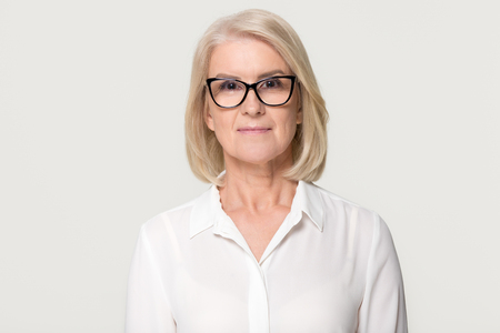 Confident older businesswoman in glasses looking at camera, middle aged senior female professional, mature lady teacher business coach head shot portrait isolated on white grey studio background