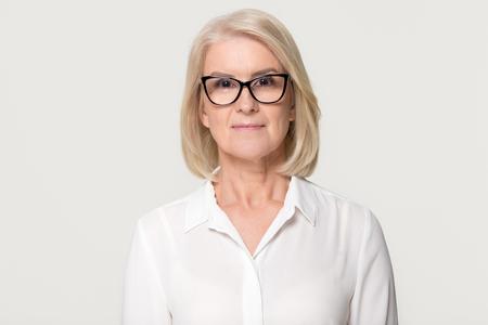 Fiduciosa donna d'affari più anziana in occhiali guardando la fotocamera, professionista femminile senior di mezza età, signora matura insegnante business coach colpo alla testa ritratto isolato su sfondo bianco grigio studio