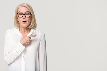 Überraschte alte reife Geschäftsfrau, die mit dem Finger auf den Kopierraum mit Blick auf die Kamera zeigt, erstaunte ältere Frau mittleren Alters in Gläsern, die den Produktservice einzeln auf weißem grauem Studiohintergrund bewerben