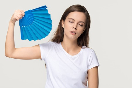 Tired young woman feel overheated suffering from heat stroke high temperature sweating problem, sweaty girl holding waving fan cooling in hot summer weather isolated on white grey studio background