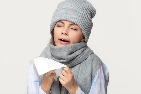 Sick young woman in winter scarf and hat holding handkerchief sneezing got flu cold symptoms, ill teen girl coughing isolated on white grey studio background, flue grippe rhinitis allergy concept
