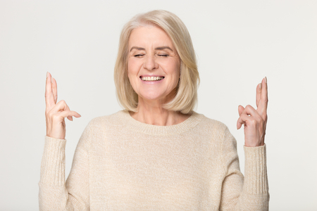 Hopeful happy middle aged old woman crossing fingers hoping for good luck, smiling mature senior lady making wish asking dream come true isolated on grey white studio background, superstition beliefs