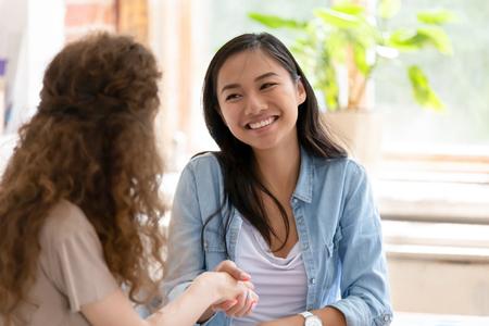 Junge verschiedene freundliche Mädchen, die sich für Hilfe bei der Teamarbeit bedanken, lächelnde, glückliche Studenten, Praktikanten, Mitarbeiter, die Hände schütteln, um eine erfolgreiche Zusammenarbeit zu feiern, zufriedene asiatische Frau, die eingestellt wird