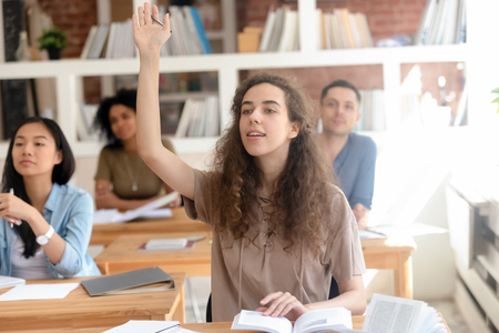 Teen female college university student raising hand during class with multinational classmate group, smart high school girl asking question at lesson sitting at desk, leadership and knowledge concept