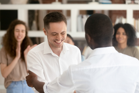 Successful caucasian worker getting promoted rewarded for professional skills handshaking african boss congratulating manager with team support, employee recognition, gratitude, appreciation bonus Stock Photo