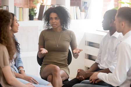 African woman psychologist coach speaking at diverse team training or group therapy session, black female trainer counseling addicted people or employees talking sharing problems sitting in circle