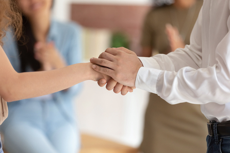 Hopeful male boss holding shaking hand promoting successful female worker employee thanking for good work, hiring, congratulating expressing respect, gratitude and trust concept, close up view