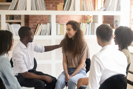 African man coach psychologist friend supporting caucasian woman sit in circle during therapy session, diverse people talking and sharing problems having group discussion helping at team counseling